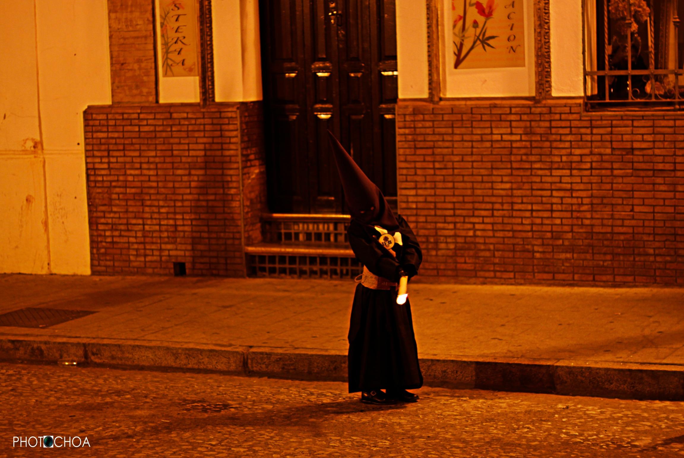 Un pequeño nazareno  se entretiene decorando el suelo empedrado